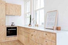 a simple neutral Scandi kitchen with plywood cabinets, white countertops and a wooden floor