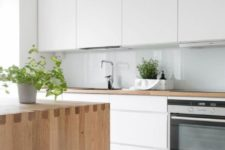 a sleek Nordic kitchen with white cabinets, a blue glass backsplash, a light stained wood kitchen island