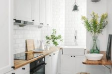 a small Nordic kitchen with white cabinets, black hardware, butcherblock countertops and white tiles plus wood and metal stools