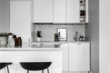 a small Nordic kitchen with white sleek cabinets and a grey stone countertop and blacksplash plus black stools