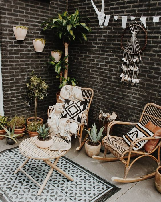 a small and cozy boho patio with rattan furniture, a dream catcher with crystals, a printed rug and pillows and potted plants