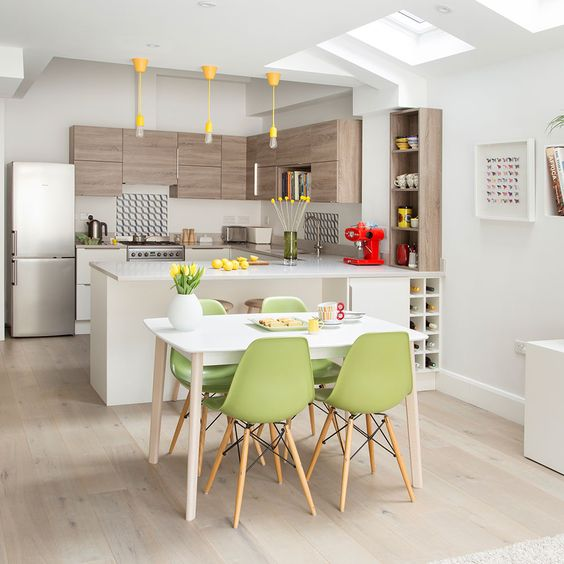 a stylish contemporary kitchen with wooden and white cbainets, with yellow bulbs, green chairs and some yellow touches