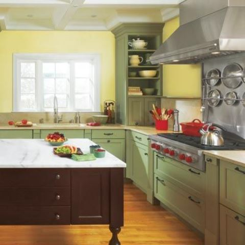 a stylish farmhouse kitchen with yellow walls, green cabinets, a dark kitchen island and a stone countertop