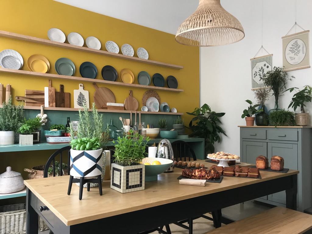 a stylish kitchen with mustard walls, green tiles on the backsplash and floating shelves