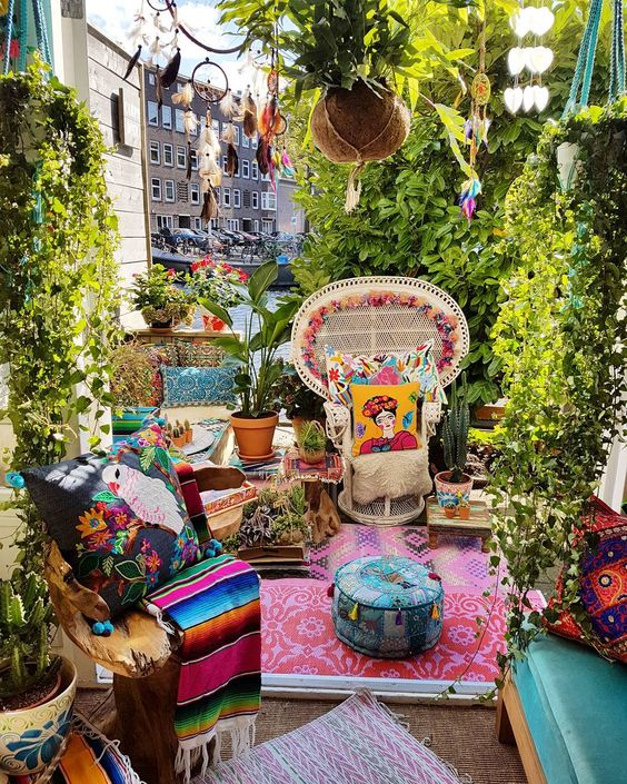 a super colorful boho patio with bright pillows, rugs, blankets, dream catchers and printed rugs