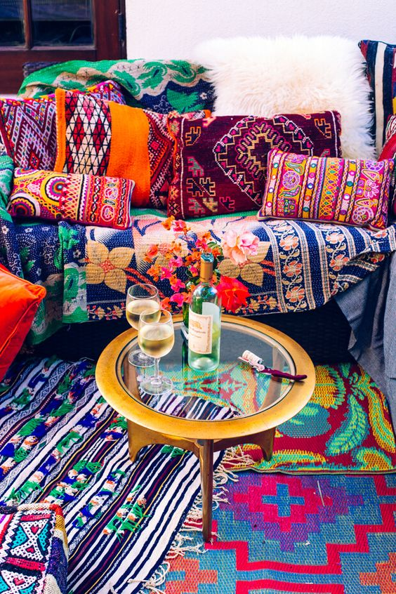 a super colorful boho space with printed pillows and rugs and a metal coffee table with a glass tabletop