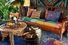 a super colorful living room with carved furniture, colorful textiles and potted plants here and there
