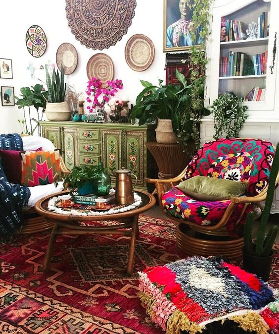 a very bright living room with colorful rugs, cushions and pillows, baskets on the wall and painted furniture