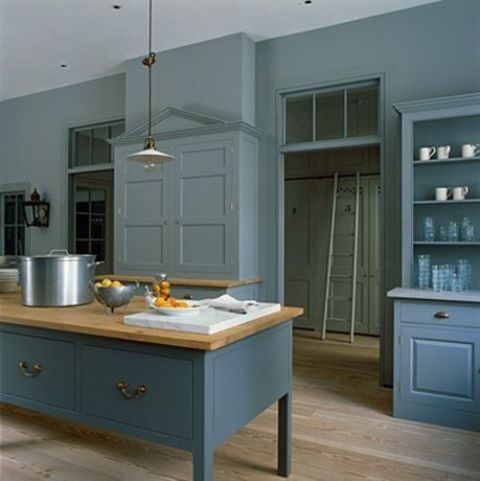 a vintage blue kitchen with paneled cabinets, wooden countertops and pendant lamps