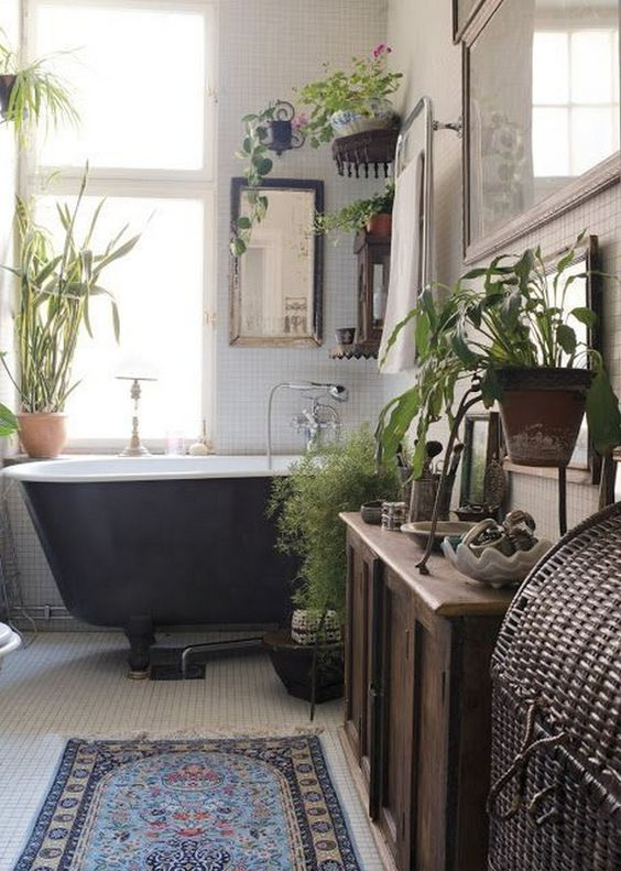 a vintage boho bathroom with a black tub, potted greenery, a stained cabinet and a boho rug
