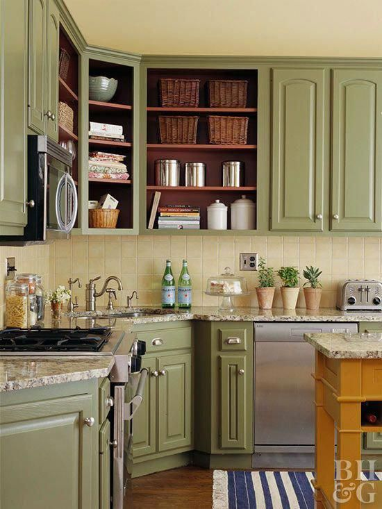 a vintage farmhouse kitchen with soft green cabinets, a light yellow tile backsplash and stone countertops