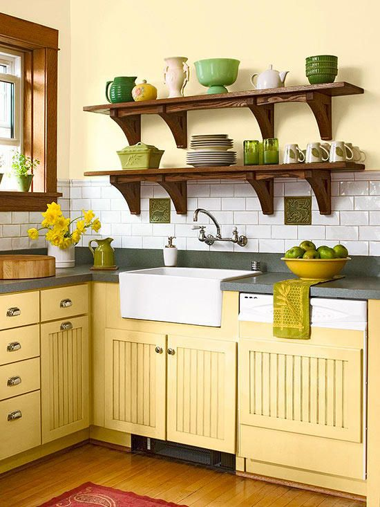 a vintage farmhouse kitchen with yellow cabinets, grey stone countertops, open shelving with green tableware and green textiles