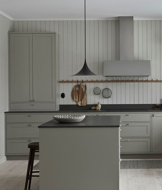 a vintage grey kitchen with elegant cabinets, black countertpos, a black pendant lamp and a shiplap wall