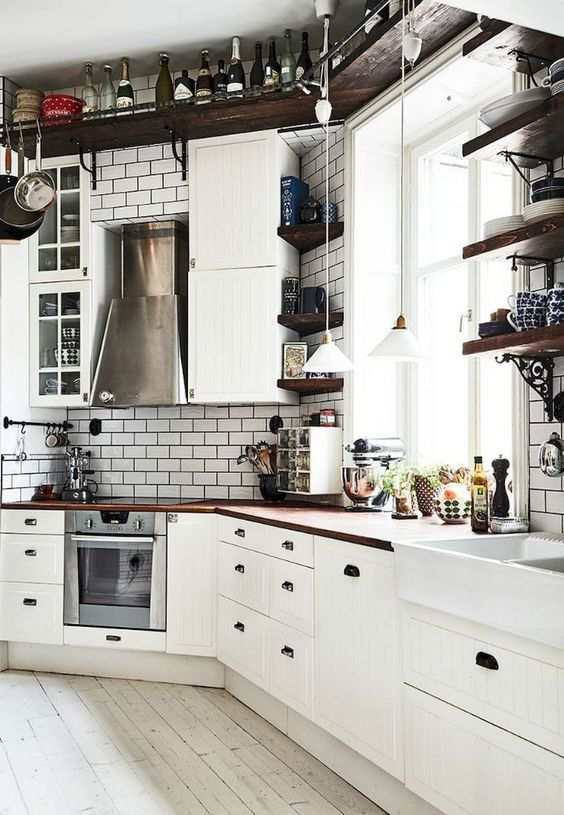 a vintage inspired Nordic kitchen with a ceiling shelf, white tiles, white vintage cabinets and rich stained countertops