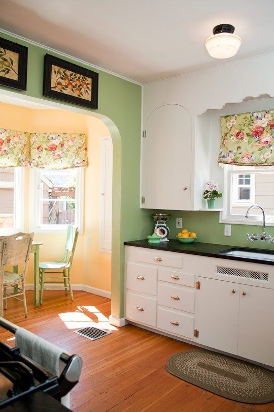 a vintage-inspired kitchen with green walls, white cabinets with black countertops, a yellow bay window with green dining furniture