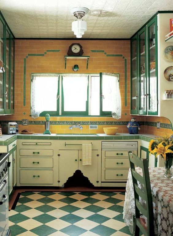 a vintage kitchen with a yellow subway tile wall, neutral and emerald kitchen cabinets and a checked kitchen floor