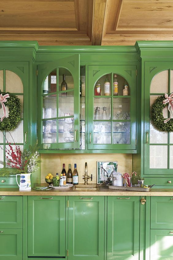 a vintage kitchen with green cabinets, tan stone countertops and a backsplash plus bold blooms