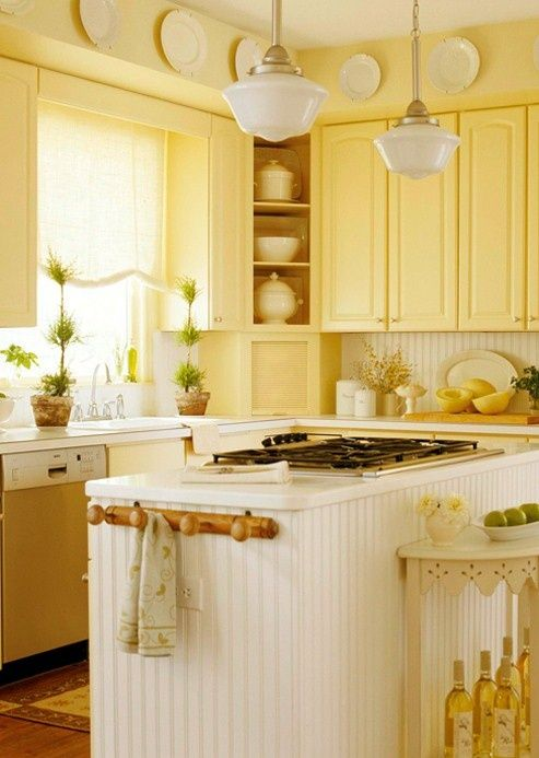 a vintage kitchen with light yellow cabinets, a beadboard backsplash and kitchen island plus potted greenery and accessories