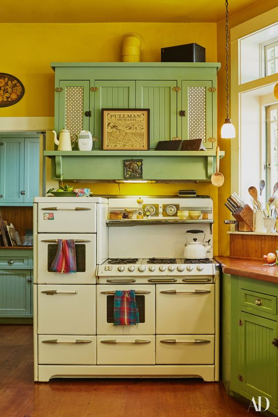a vintage kitchen with mustard walls, vintage green cabinets, neutral appliances and pendant lamps