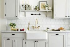 a vintage neutral kitchen with elegant cabinets, a white tile backsplash, a colorful tile floor and black wall lamps