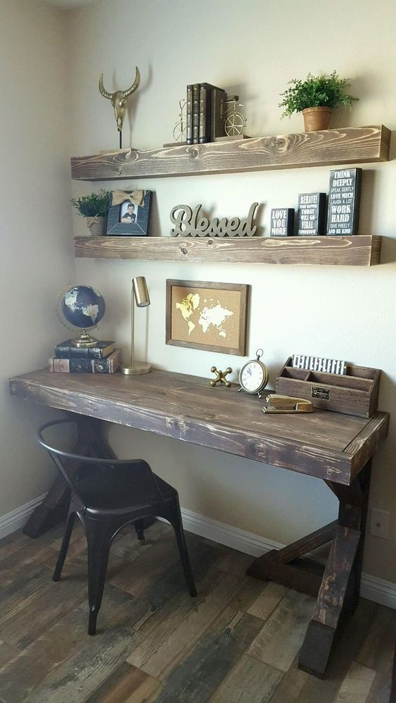 a vintage rustic home office with open shelves, a dark stained desk, a black chair and some decor