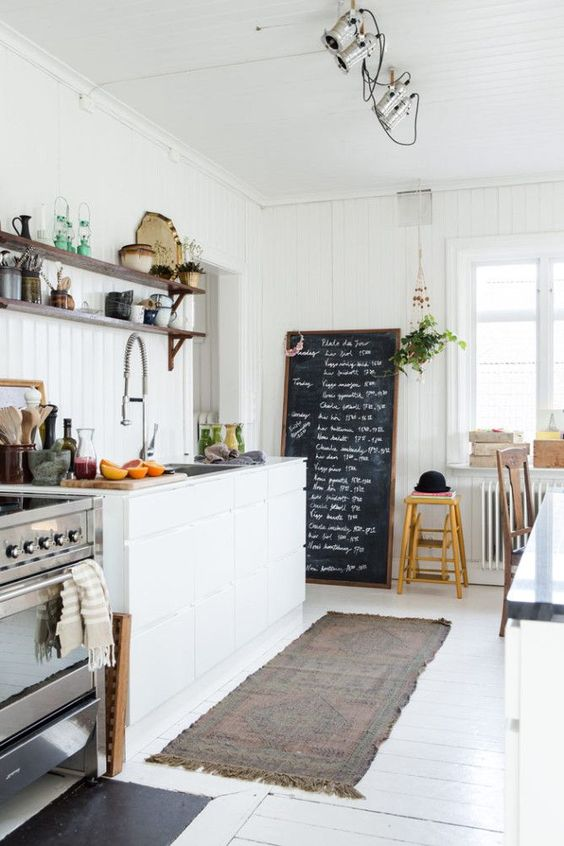 a welcoing and light-filled Nordic kitchen with shiplap walls, a white floor, a chalkboard and sleek cabinets plus lights