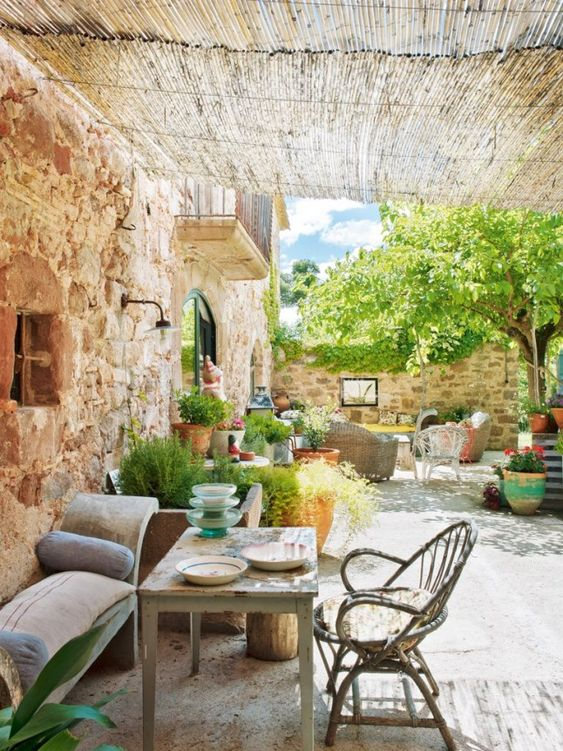 a welcoming rustic patio in Spanish style, with stone walls, rattan and wooden furniture and potted greenery and blooms