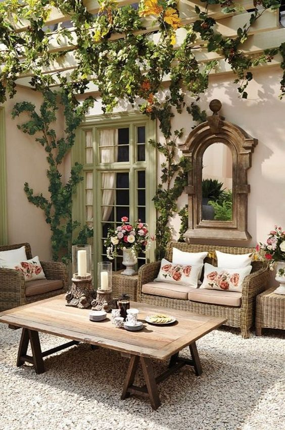 a welcoming rustic patio with wicker and wooden furniture, lot sof vines and a vintage mirror in a wooden frame
