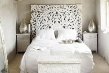 a white Moroccan bedroom with a carved headboard, chest and nightstands, silve rlanterns and a jute rug