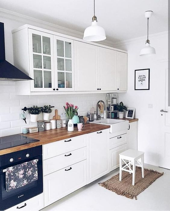 a white Scandi kitchen with vintage-inspired cabinets and black hardware, butcherblock countertops and pendant lamps