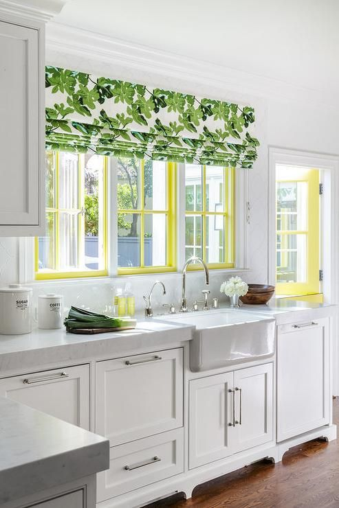 a white cottage kitchen with a yellow frame window and a botanical print curtain plus a yellow door
