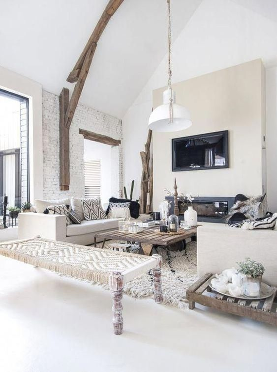 a white rustic living room with a built-in fireplace, a wooden beam with a pendant lamp, rough wood tables and a woven daybed