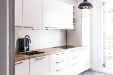 an airy Scandinavian kitchen with white cabinets, butcherblock countertops, a geometric floor and pendant lamps