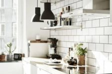 an airy kitchen with white tiles, white cabinets, wooden countertops, black pendant lamps