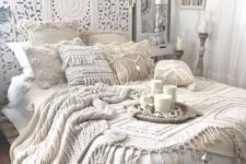 an all-white Moroccan bedroom with an ornate wodoen screen, crochet pillows and blankets, candles and lanterns and dream catchers