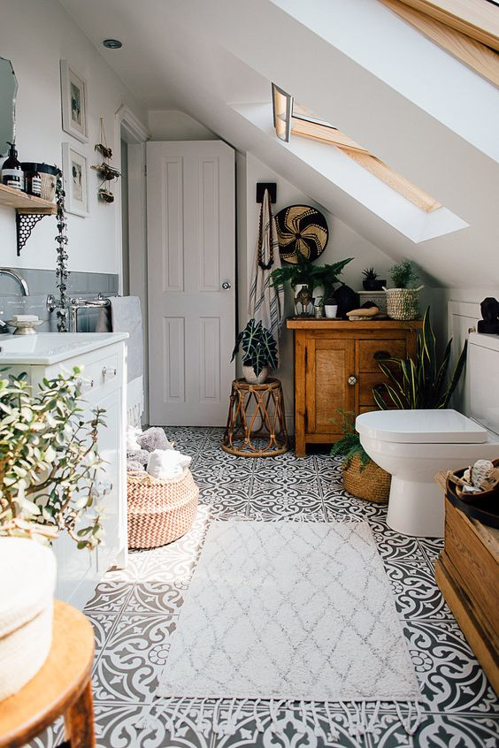 an attic boho bathroom with a wooden cabinet, a rattan side table, a basket and some potted plants