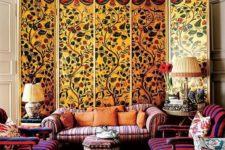 an extra colorful living room with striped furniture, colorful rugs and pillows and a painted screen