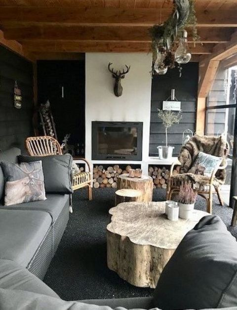 an outdoor living room with a fireplace, a deer head, a tree stump table and upholstered furniture