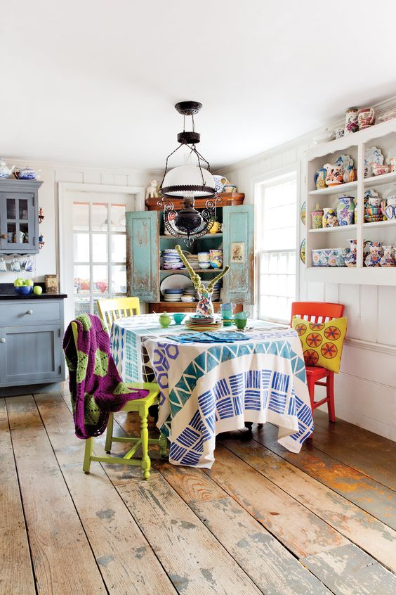 blue cabinets, a turquoise sideboard and colorful chairs, textiles and porcelain