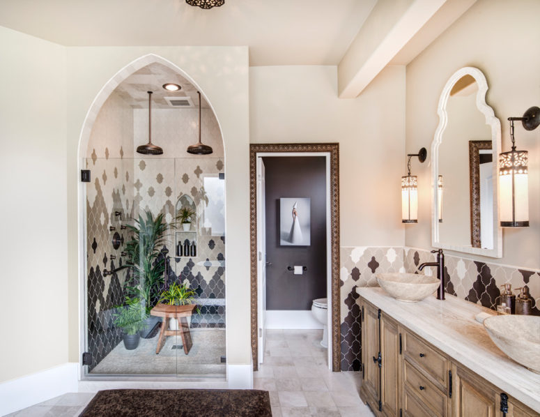a Moroccan master bathroom includes a hand-carved wood vanity made in Morocco and black and white Moroccan tiles arranged in a catchy way  (Harjo Construction)