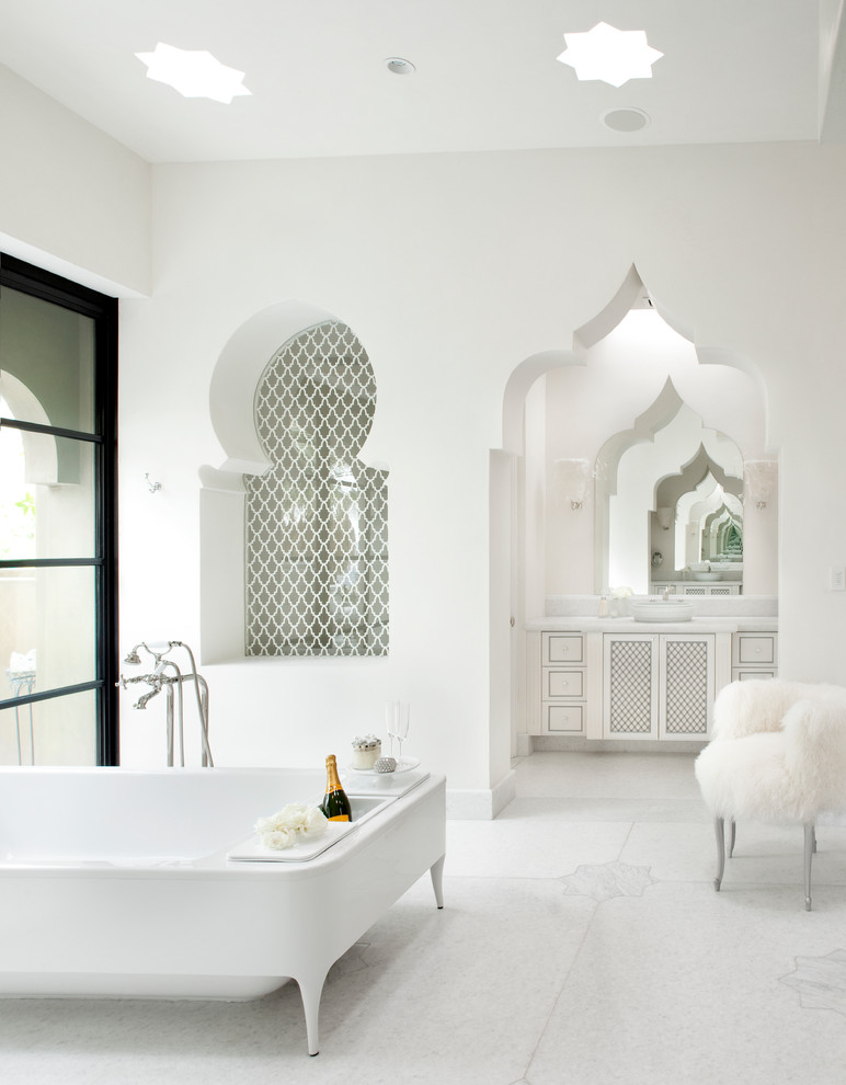a pure white bathroom with star-shaped skylights, a tiled niche and a cutout doorway plus a carved vanity  (Gordon Stein Design)