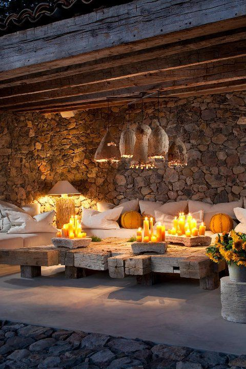 stone walls, a tiled floor, upholstered furniture, wicker lampshades and a low wooden table