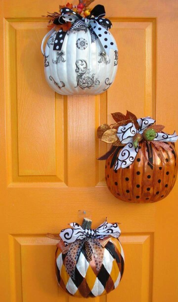 Dollar store pumpkins could be decorated and hanged on a door.