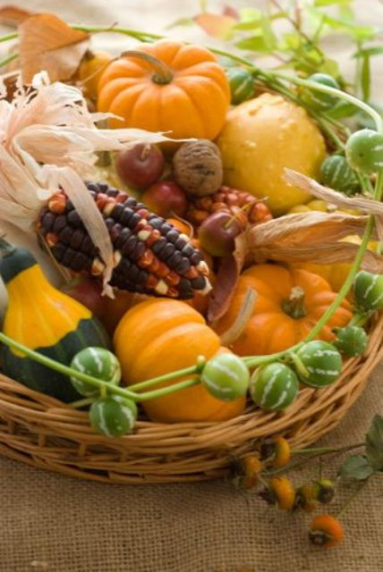 a basket with corn, pumpkins, gourds and husks for a long-lasting fall centerpiece to use more and more