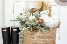 a basket with white, striped and rust velvet pumpkins and greenery plus rubber boots for cool fall decor