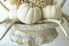 a beautiful fall arrangement of a vintage urn with white pumpkins, antlers and bleached pinecones is very chic