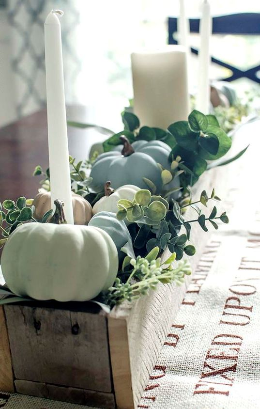 a beautiful pallet box fall centerpiece filled with chalk painted pumpkins, greenery and candles is stylish