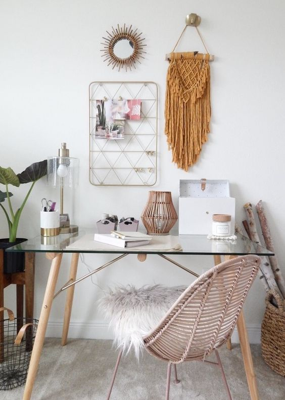 a boho chic home office with a glass desk, a rattan chair, a rattan lantern, a macrame hanging, a sunburst mirror, a memo board and some potted plants
