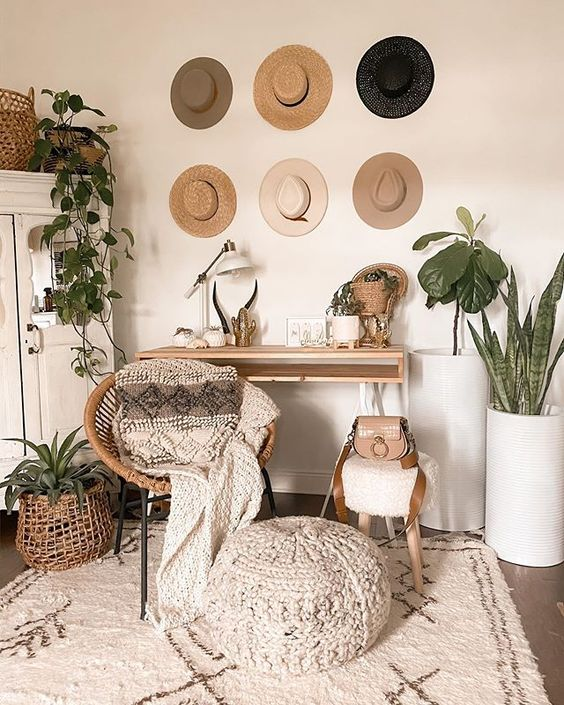 a boho chic home office with a sleek desk, a rattan chair, a wooden sotol and a woven ottoman, potted plants and hats on display
