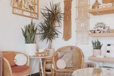 a boho chic home office with rattan furniture, open shelving, macrame hangings and a botanical poster, potted plants and round pillows